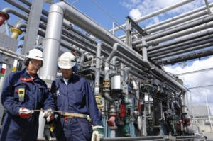 Energy sector training with two employees in front of equipment