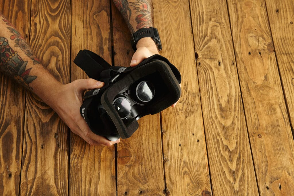 Man holding a VR headset. Find the right VR headset to prevent motion sickness in VR.